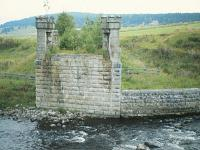 The castellated southern abutment of the Dulnain Bridge in August 1982 in a view looking to Broomhill. The girders had been removed after closure in 1965 and it would be another thirty three years before the new girders were laid by the Strathspey Railway as they reconstructed the line to Grantown-on-Spey. [See image 46310]<br> <br><br>[Peter Todd&nbsp;/08/1982]