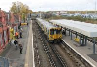 A Merseyrail service heading for Liverpool calls at Birkenhead North, where a number of original station buildings are still in use. Just beyond the bridge is Birkenhead North EMU Depot, and some of the buildings can be seen above the car park.<br><br>[Mark Bartlett&nbsp;16/11/2015]