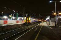 A pair of Northern Class 150s at Leyland after dark on 7 December 2015. The two green columns on the left (platform 4) are supports for the new footbridge and steps, scheduled for installation over the Christmas shutdown period.<br><br>[John McIntyre&nbsp;07/12/2015]
