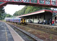 A FGW 150/153 combination slows for the stop at Torre heading for Torquay and Paignton on 26th July 2015. Although the station canopy still shelters the Down platform the station building itself is in commercial use, accessed from the forecourt.<br><br>[Mark Bartlett&nbsp;26/07/2015]