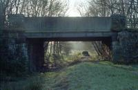 The site of Killearn station in 1990. The station (which was largely timber) closed to passengers in 1951 and little survives apart from a stationmaster's house and this overbridge (since replaced). [See image 6772] [Ref query 36140]. The few remains at the site were largely removed during the construction of the Loch Lomond Water Supply Scheme.<br><br>[Ewan Crawford&nbsp;//1990]