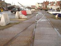 Looking seaward along the disused and disconnected tracks running along Whitby's Endeavour Wharf. The lines ran between the river and a large transhipment shed, enabling wagons to be loaded direct from seagoing vessels or from the shed itself. As the wharf has been out of use commercially for over a decade the goods shed has been demolished, and the cleared area is now used mainly for car parking. <br><br>[David Pesterfield&nbsp;13/12/2015]