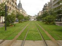 View north north west along Cours Jean-Baptiste Langlet of a scenic section of the light rail tram network that crosses Reims from north east to south west of the city. This city centre section does not use overhead catenary, instead appearing to use a mid track induction pick up arrangement to avoid marring views of Reims Cathedral, a short distance to the rear. Langlet tram stop is just beyond the van crossing the tracks ahead.  Immediately behind the camera is a temporarily closed section due to rebuilding of the area around the Opera tram stop on Place Myron T Herrick.<br><br>[David Pesterfield&nbsp;24/07/2015]
