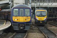 Units at Piccadilly - 319368 calls at platform 13 with a Liverpool Lime Street to Manchester Airport Northern Electrics service. On the right 185150 enters the main station with a TPE service that is also heading to the Airport but will reverse first.<br><br>[John McIntyre&nbsp;10/12/2015]