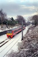 320.307 passes the site of Milngavie signalbox early in 1991. The line had recently been singled, thus the approach 'wrong line' to the station, and snow can be seen on the disused rails to the right.<br><br>[Ewan Crawford&nbsp;//1991]