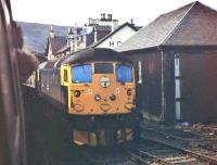 Kyle line services cross at Achnasheen in 1977. Viewed from a BRC&W Class 26 hauled westbound service, a classmate heading for Inverness is seen. Alongside the loco is the now demolished goods shed with the station hotel (later burnt down) behind. <br><br>[Mark Bartlett&nbsp;13/09/1977]