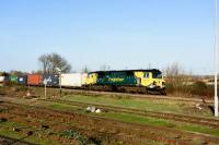 Freightliner 70011 takes an eastbound Freightliner past Didcot station on 23rd December 2015. <br><br>[Peter Todd 23/12/2015]
