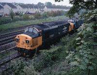 37085 and a fellow Eastfield based 37 draw a long oil train out of Bishopbriggs Oil Depot in 1987. [See image 53783] for the same view in 1971.<br><br>[Ewan Crawford&nbsp;27/05/1987]