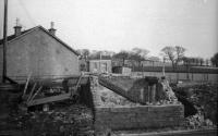 This is the remains of the former Ardmore Level Crossing SB after it was destroyed by fire in the early 1970s. At the time the box had been in use as a PWay bothy and store, having been replaced by a new box diagonally across the LC (out of shot to the left) in 1943 when the Ardmore marshalling yard was opened. That box closed in 1976. Today there is only an REB to house the equipment for the AHB level crossing.<br><br>[John McIntyre&nbsp;//]