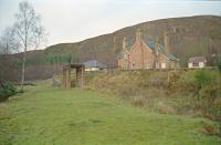 The Mound seen from the trackbed of the Dornoch Light Railway in 1998. The station platform can be seen in the distant left. The 'mainline' is beyond the station building seen to the right. Base of water tank to the right of the branch trackbed.<br><br>[Ewan Crawford&nbsp;//1998]