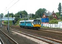 A Newcastle - Sunderland service passing Pelaw in July 2004, seen from the Metro station platforms. The former station master's house (since demolished following a fire) stands in the background. [Ref query 50469] <br><br>[John Furnevel&nbsp;10/07/2004]