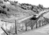 Looking east towards the site of Stannergate station (closed 1916) between Dundee and Broughty Ferry in 1981, with an Aberdeen - Kings Cross HST approaching. The bridge linking the A92 (behind the trees on the left) and Stannergate Road has since been closed. The pylons visible have also gone, following the closure of Carolina Port power station on the other side of the bridge [see image 36084]. [Ref query 15197]<br><br>[John Furnevel&nbsp;11/08/1981]