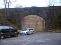 View north east at the bricked up south portal of the very high Heys Road over-bridge at Thongsbridge near Holmfirth, beyond which new housing is being built in the deep cutting running to the nearby Springwood Road over-bridge. The roofs of those by the bridge can just be seen rising above the parapet. Other than the A616 rail overbridge near Brockholes, these two bridges are the only other structures extant on the former Holmfirth branch in March 2016. <br><br>[David Pesterfield&nbsp;03/03/2016]