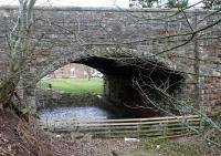 The tail of the platform still remains under Station Road at Gordon. This view looks under the bridge at the station and towards Duns.<br><br>[Ewan Crawford&nbsp;06/03/2016]