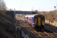 A Glasgow Queen Street to Falkirk Grahamston service on the crossover approaching Cowlairs South Junction passes under Fountainwell bridge which is due to be demolished shortly (March 2016.) Photographed from Sighthill cemetery grounds. <br><br>[Colin McDonald&nbsp;14/03/2016]