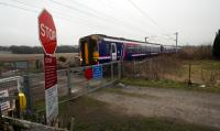 Northbound service from Queen Street to Oban, Fort William and Mallaig passes Geilston Level Crossing and its ample warning signage.<br><br>[Ewan Crawford&nbsp;18/03/2016]