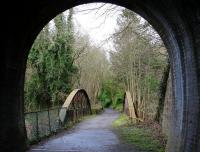 On leaving the west portal of Auchendinny tunnel, trains on the Penicuik Railway crossed a bowstring girder bridge over the North Esk before reaching the station. The surviving platform stands on the left immediately beyond the bridge in this view from the tunnel on a bright but chilly morning in March 2016. The route now forms part of a walkway.  <br><br>[John Furnevel 28/03/2016]