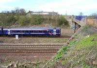 The 0845 Tweedbank - Edinburgh about to pass below Whitehill Road bridge as it slows for the stop at Newcraighall station on 17 April 2016. A photograph from this position has only recently become possible following the cutting back of trees and shrubs along the embankment running south from the bridge towards Millerhill Yard.<br><br>[John Furnevel&nbsp;17/04/2016]