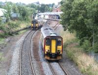 A pair of ScotRail class 156 DMUs passing just north of Dumfries station on 30 July 2004. A Stranraer Harbour – Newcastle service is about to call at the station, while the northbound train has just restarted its journey from Carlisle to Glasgow Central and is about to pass below the bridge carrying the A701.<br><br>[John Furnevel&nbsp;30/07/2004]