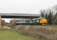 The <I>Bay Gateway</I> bridge over the WCML is an impressive structure but was only carrying construction traffic when 37402 propelled the Carlisle to Preston service under it on 1st April 2016. A short distance to the east another bridge carries the new road over the Lancaster Canal. What appears to be a single yellow signal is actually a flashing aspect indicating the next signal is also on yellow but the train is routed into the speed restricted Platform 4 line at Lancaster.<br><br>[Mark Bartlett&nbsp;01/04/2016]