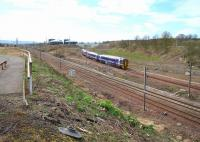 Looking south towards Millerhill Yard on 17 April 2016, showing the considerable clearance of vegetation that has recently been carried out along the embankment. The entrance to the depot from Whitehill Road is on the left. In the background a Waverley bound train is approaching from the Shawfair direction.<br><br>[John Furnevel&nbsp;17/04/2016]