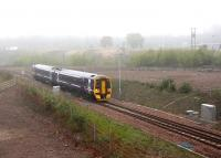 ScotRail 158736 emerges from the fog at Millerhill on Sunday 8 May 2016 with the first Borders Railway southbound train of the day, the 0911 Edinburgh – Tweedbank. The train is in the process of passing over the double-track split at Newcraighall South Junction. In less than half a mile it will reach Shawfair station where it is scheduled to cross the first train north, the 0845 Tweedbank - Edinburgh. Part of the Millerhill Yard admin block is just visible in the right background. <br><br>[John Furnevel&nbsp;08/05/2016]