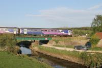 A pair of Class 153 single units cross a low bridge near Silverdale with a Barrow-in-Furness to Lancaster service on 12th May 2016. The watercourse in the foreground drains the nearby Leighton Moss RSPB reserve. <br><br>[Mark Bartlett&nbsp;12/05/2016]