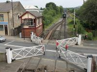 A once common sight that is very rare now. The signalman at Ramsbottom has released the pedestrian wicket gates and winds the wheel to open the level crossing to road traffic as a passenger train disappears towards Rawtenstall. During the early 1960s this box was open 24/7, apart from a few hours overnight Sunday to Monday, and the line was busy with freight, parcels and passenger trains.<br><br>[Mark Bartlett&nbsp;26/07/2014]