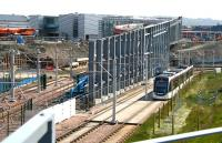 A tram heading for Edinburgh Airport runs west through the site of the under construction Edinburgh Gateway station on 7 June 2016. The bridge linking the rail and tram sides of the interchange has recently been installed. Edinburgh Gateway is scheduled to become operational by the end of 2016<br><br>[John Furnevel&nbsp;07/06/2016]