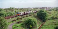 Class 56110 passing Stevenston with a loaded coal train from Hunterston in 1999. Behind the 3rd and 4th wagons (from the left) is the abutment of the Caledonian flyover.<br><br>[Ewan Crawford&nbsp;//1999]