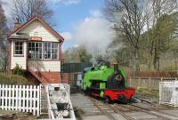 0-6-2ST <I>Barber</I> runs past the signal box at Alston in May 2016 as it draws forward to couple on to its train after running round. It seems to be semi-permanently coupled to a four wheel hopper wagon, emblazoned with <I>GAS</I>. This may be just in homage to the loco's working life at Harrogate Gas Works, but it may also be a nice solution to the problem of where to put the air brake compressor for the STR coaches.<br><br>[Mark Bartlett&nbsp;02/05/2016]