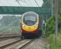 A London bound Pendolino passes Euxton on 11 June 2016. Euxton Jct is behind the train to the left as it crosses a minor road on structure 89. The footbridge behind is structure 90.<br><br>[John McIntyre&nbsp;11/06/2016]
