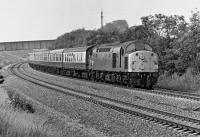 When Healey Mills based EE Type 4 No. 40 048 passed me at 10:23 on the morning of Saturday 2 August 1975 near Oakenshaw North Junction with a rake of Mk 1 coaches in tow, I assumed that this was an excursion to the Yorkshire coast. However, after perusing the 1975 BR timetable recently in the NLS, I have now concluded that the train is actually the dated 09:42 SO Sheffield to Glasgow, the successor to the 06:40 SO Birmingham to Glasgow, a train of some renown in 1966/67 because of its 'Jubilee' haulage over the S&C. In 1975 the class 40 no doubt gave way to a Holbeck based class 45 at Leeds.<br><br>[Bill Jamieson&nbsp;02/08/1975]