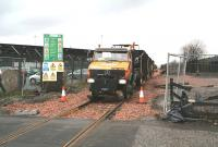 A roadrail Unimog vehicle about to bring ballast wagons east over Cambus level crossing in December 2006 during reinstatement of the Stirling - Alloa line. Part of the huge Diageo site stands in the background..<br><br>[John Furnevel&nbsp;15/12/2006]