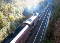 An EWS class 66 with a coal train on the sub in October 2003. The train is climbing past the remains of Craiglockhart station having just emerged from the tunnel under the Union Canal.<br><br>[John Furnevel&nbsp;06/10/2003]