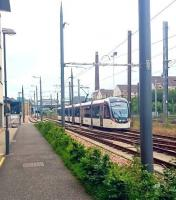 A westbound tram shortly after leaving Haymarket heading for its next stop at Murrayfield Stadium on 4 July 2016. The road on the left is Haymarket Yards, site of the former goods and coal depots, while on the right beyond the fence is the E&G main line. Haymarket station stands in the background.<br><br>[Andy Furnevel&nbsp;04/07/2016]