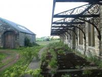 Scene at Whittingham station, Northumberland, on 29 May 2004. View is north along the island platform towards Wooler, with the old goods shed standing on the left. Whittingham station closed to passengers in September 1930.<br><br>[John Furnevel&nbsp;29/05/2004]