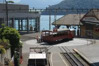 The compact arrangements at Vitznau, on the shore of Lake Lucerne. The depot is accessed by the turntable, which has a straight and curved line and is kept busy throughout the day. Here a vintage carriage that has just returned from a charter trip to Rigi summit is returned to its depot road by the resident shunter. The rail platforms are in the foreground with the ornate lake steamer station behind.<br><br>[Mark Bartlett&nbsp;27/06/2016]