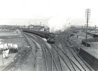 A Winton Pier - Glasgow St Enoch train about to pass through Holm Junction on 6 July 1959. Corkerhill Standard class 5 4-6-0 73103 is at the head of the train. [Railscot note: No doubt the lady in the garden on the left had checked the wind direction first thing that particular Monday morning].     <br><br>[G H Robin collection by courtesy of the Mitchell Library, Glasgow&nbsp;06/07/1959]