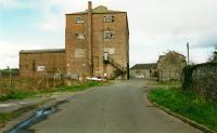 Garlieston Mill was served by the Millisle-Garlieston line which continued beyond the passenger terminus at Garlieston to the mill and pier. The track was to the left in this 2002 view. [See image 2112].<br><br> <br><br> The mill has since been demolished however the two storey building to the right and that straight ahead at the pier remain in a new development here.<br><br>[Ewan Crawford&nbsp;//2002]