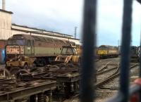 Another class 47/4 seen through the gates of Nemesis Rail at Burton-upon-Trent, along with a backhoe loader and an industrial shunter (just visible on the right).<br><br>[Ken Strachan 09/07/2016]