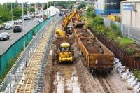 Weekend engineering possession at Chorley on 30 July 2016. In this view north from Lyons Lane bridge towards the station, the down line is being lowered and the temporary platform on the left has been adjusted so that it is clear of the diggers which are loading the train of JNA wagons on the right. The work is in connection with the electrification of the line from Manchester.<br><br>[John McIntyre&nbsp;30/07/2016]