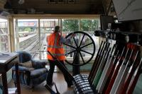 Signalman Peter Bendall winds the wheel in Ramsbottom signal box to close the level crossing gates to road traffic on 3rd August 2016. Peter believes these are the only wheel operated gates on a UK heritage railway so they are a cherished asset, if a little heavy to work. The large windows give excellent views of the railway and also the road on both sides of the crossing. Image taken with kind permission of the East Lancashire Railway during a supervised visit.  <br><br>[Mark Bartlett&nbsp;03/08/2016]