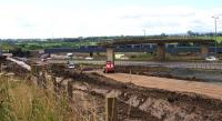 Partly obscured by the remaining spans of the former Bredisholm Road bridge over the A8, a diverted Class 170 DMU speeds across the Bargeddie Bridges. In the foreground the new alignment for the A8 takes shape; the new section of the M8 will run alongside it, cutting through the present dual carriageway after passing under the new railway viaduct opened in 2015 [see image 46140].<br><br>[Colin McDonald&nbsp;29/07/2016]