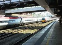 A Pendolino on the down fast passes a Euston-bound set stopped at platform 1. The weather in Stafford is not always so clement [see image 30491]<br><br>[Ken Strachan&nbsp;16/04/2016]
