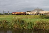 The thrice weekly Clitheroe to Mossend cement tanks will run via the WCML throughout 2016. 66099 powers north alongside the Lancaster Canal between Brock and Garstang & Catterall on the evening of 12th August 2016. The dome behind the tanks is the salt store of the Highways Agency depot for the nearby M6 motorway.<br><br>[Mark Bartlett&nbsp;12/08/2016]