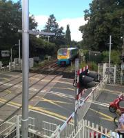 A midday Sunday service to Manchester Piccadilly passes the full paraphernalia of a modern level crossing as it slows for Nantwich station on 7 August 2016.<br><br>[Ken Strachan&nbsp;07/08/2016]