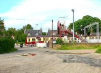 Passengers exit Cardross station via the pedestrian footbridge on 27 July 2005, having recently disembarked from a Helensburgh bound train. The motor cyclist is forced to wait for the train to clear the level crossing before recommencing his journey. View north along Station Road towards the junction with the A814. <br><br>[John Furnevel&nbsp;27/07/2005]