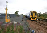 Seen looking west from the corner of the SPT car park at Shotts on 31 August 2016, a Glasgow bound Class 158 DMU passes the rail access point recently constructed as part of the large contractor's compound for the works at Shotts station.<br><br>[Colin McDonald&nbsp;31/08/2016]