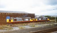 On a cloudy summer's day at Blackburn Station two BR Type 3 Class 37s (37379 and 37370) in BR Railfreight livery sit beside the old Goods Shed-which company built the shed, L&Y, B&P or some other? <br> Nowadays this site is occupied by a Vue multiscreen cinema.<br><br>[Charlie Niven&nbsp;/06/1989]